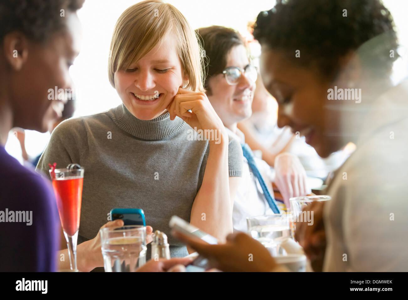 La vie en ville. Un groupe de personnes dans un café, la vérification de leurs téléphones intelligents. Photo Stock