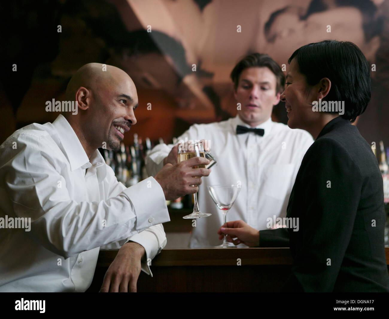 Un jeune homme et femme assise dans un bar boire ensemble Photo Stock
