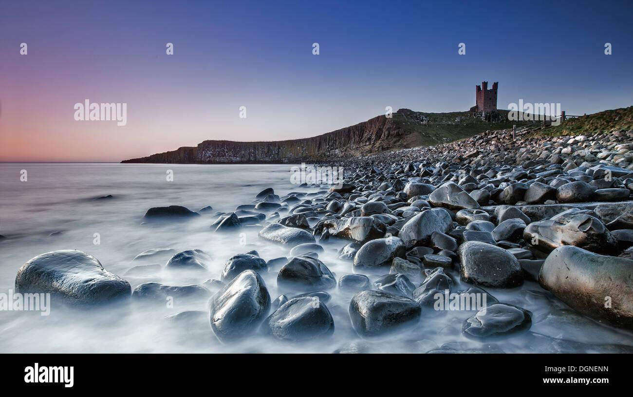 Plage de galets avec des ruines de château en arrière-plan Photo Stock