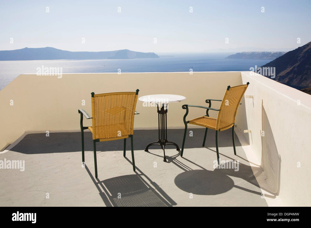 Deux chaises et une table sur une terrasse donnant sur la caldeira de Fira et la mer Égée, Santorini, Cyclades, Banque D'Images