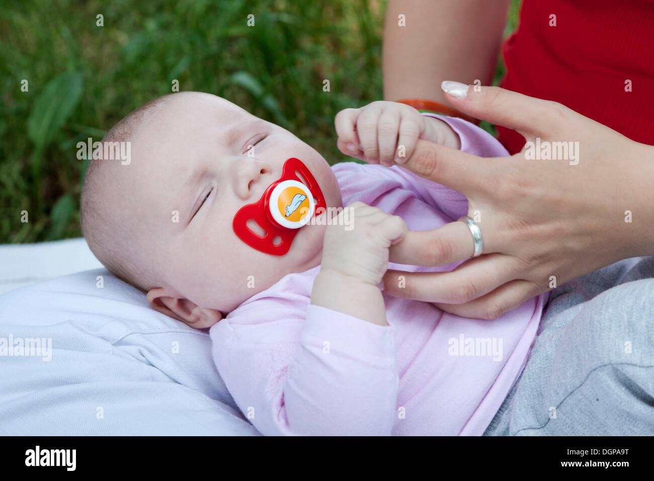 Un bébé de quelques mois, s'accrochant aux doigts de sa mère Banque D'Images