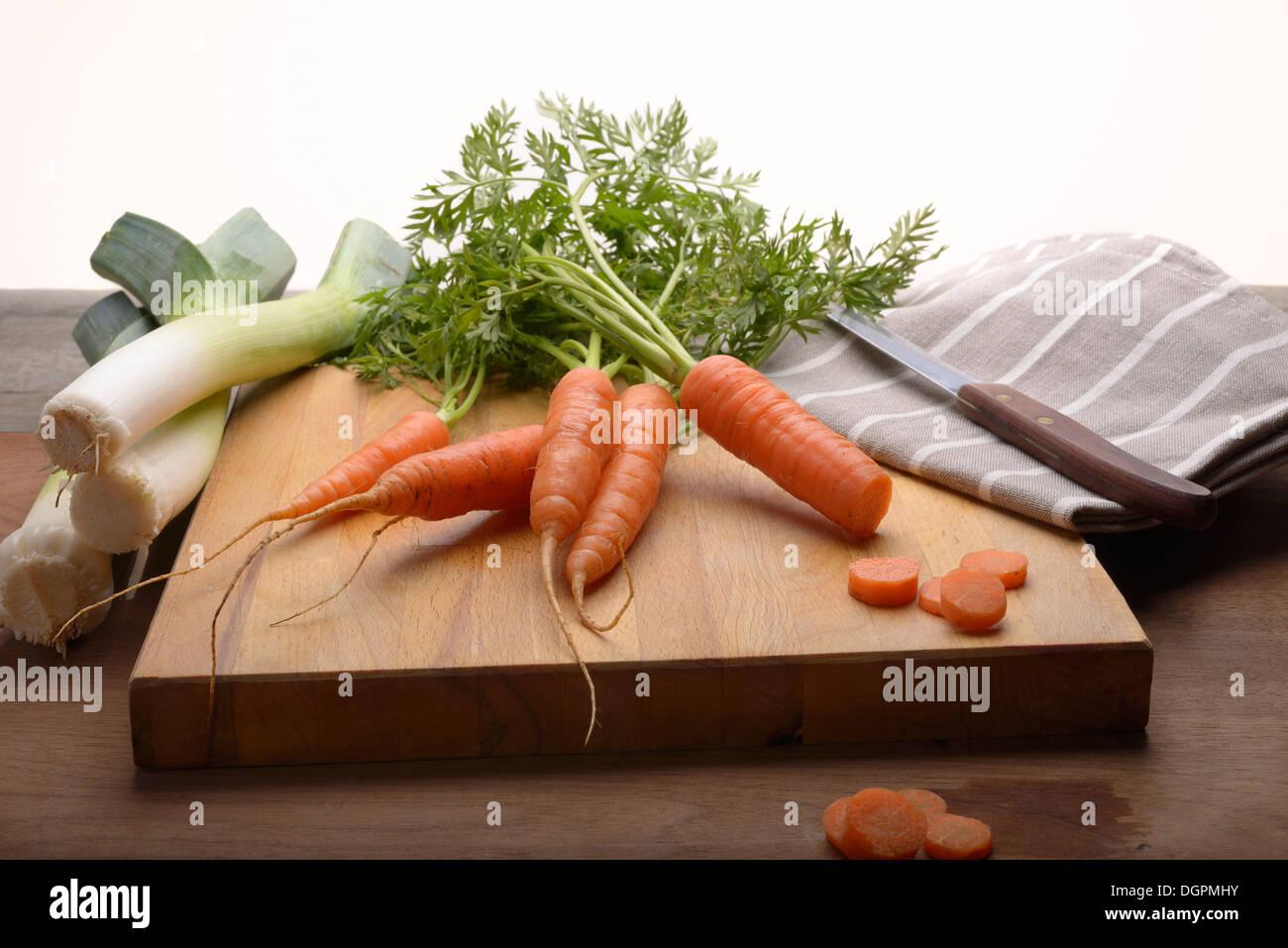 Culture biologique frais carottes et poireaux sur une planche à découper de cuisine avec un couteau et un torchon en vue Photo Stock