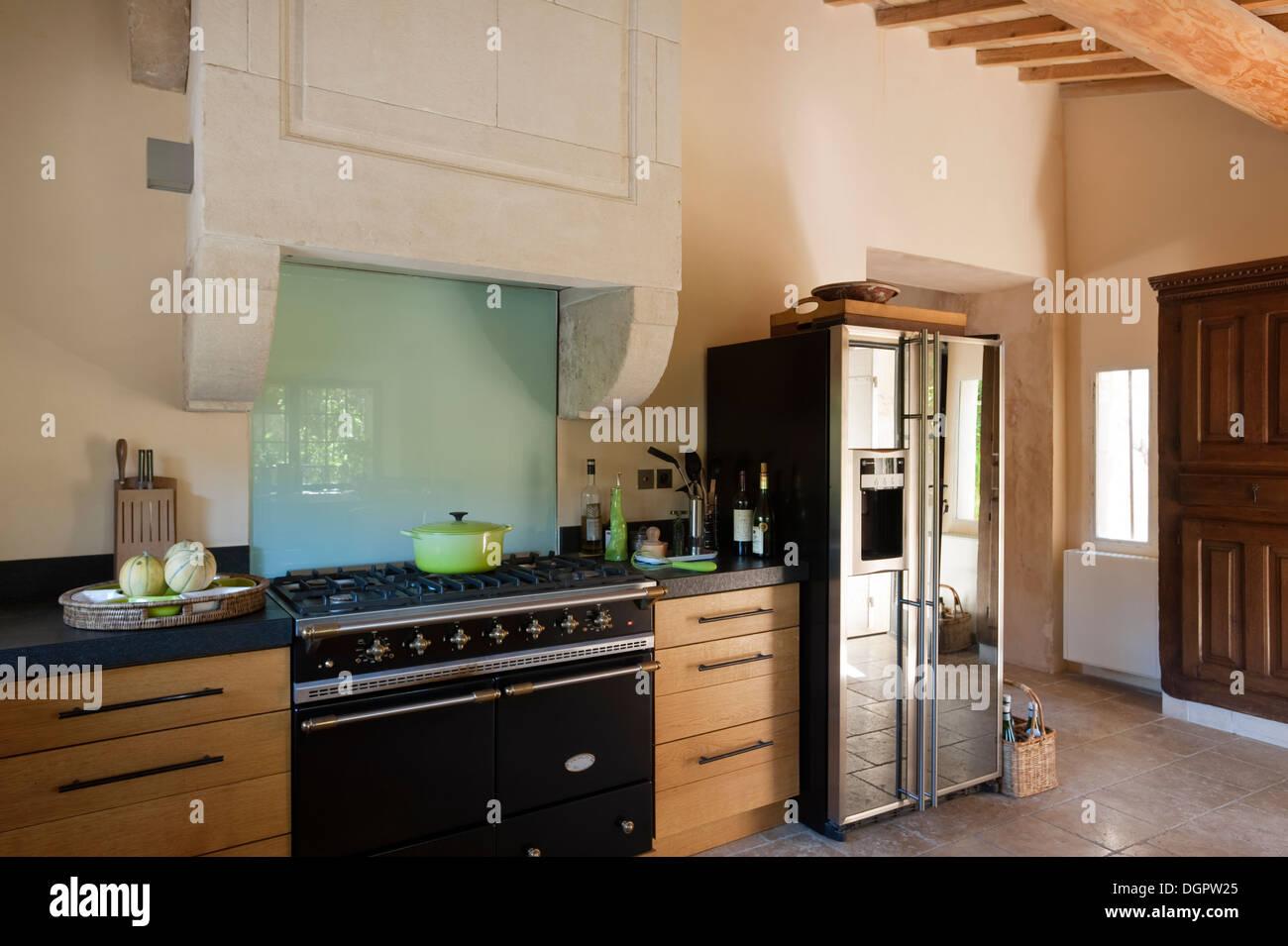 une cuisini re lacanche et une hotte en pierre encorbellements dans une cuisine avec armoires. Black Bedroom Furniture Sets. Home Design Ideas