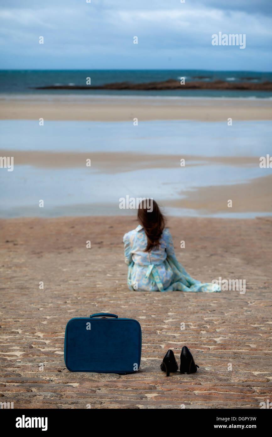 Une valise et chaussures noires sur un feuillet, dans une distance est assise une femme Photo Stock