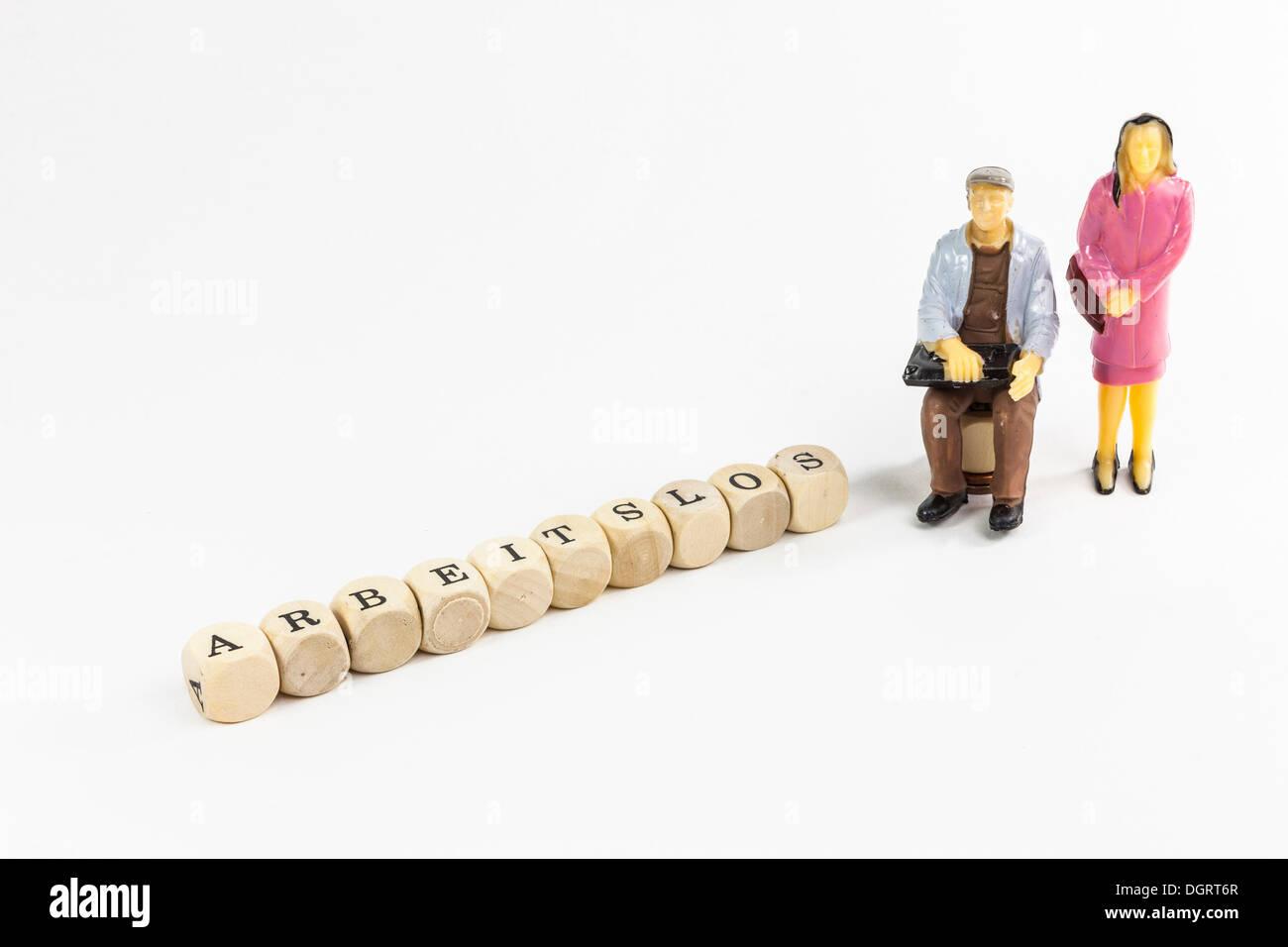 """Figures miniatures d'un couple sans emploi, lettres formant le mot """"arbeitslos', l'allemand pour les 'chômeurs' Photo Stock"""