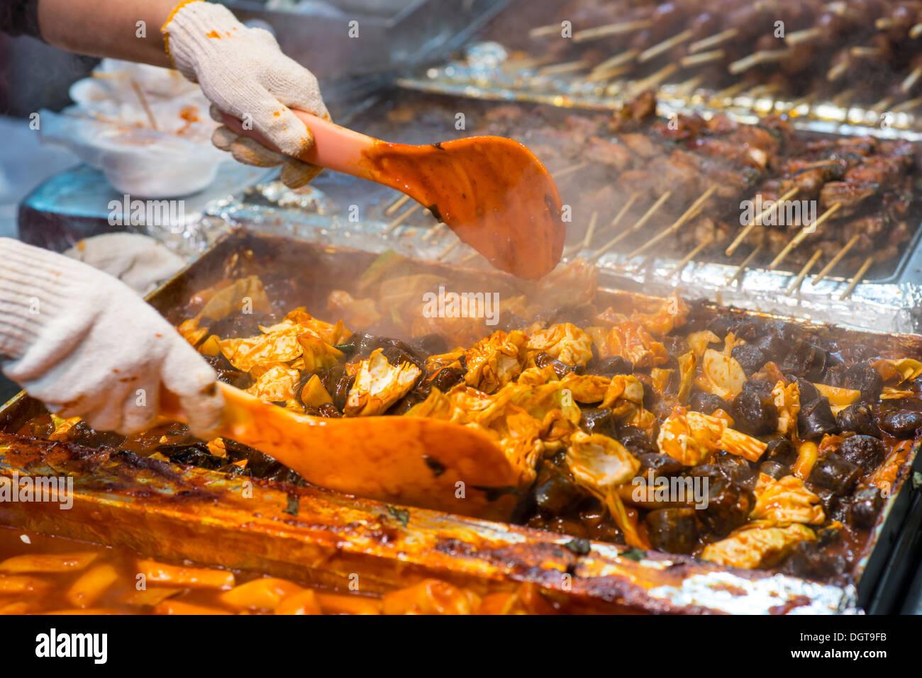 Préparation des aliments à un marché de nuit dans la région de Myeong-dong, Séoul, Corée du Sud. Photo Stock
