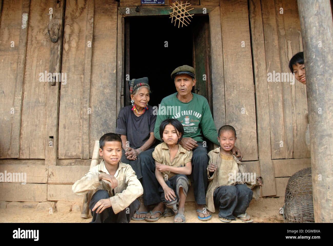 Photo de famille, grands-parents avec petits-enfants du groupe ethnique Mouchi assis à l'entrée de leur hutte portant Photo Stock