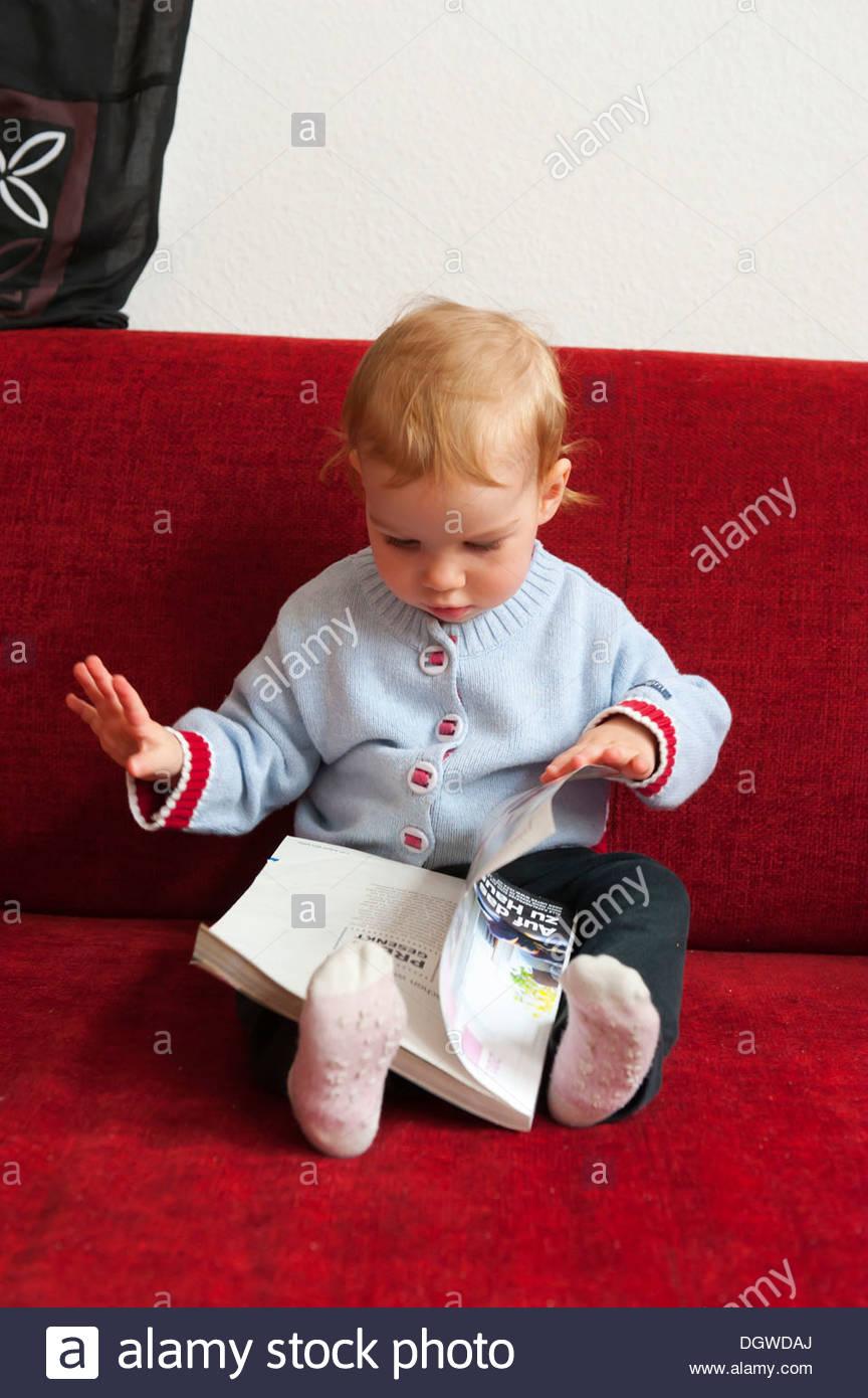 Tout-petit, fille assise sur un canapé en regardant une brochure, Munich, Bavière Photo Stock