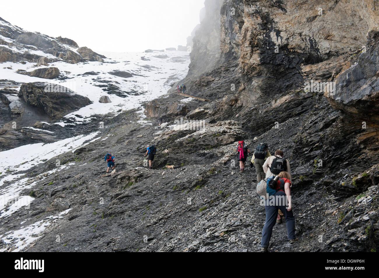 Sentier de randonnée Trek de l'ours, les randonneurs sur le chemin jusqu'à la note de passage à niveau rock sombre avec des restes de neige, Col Hohtürli, Kandersteg Photo Stock