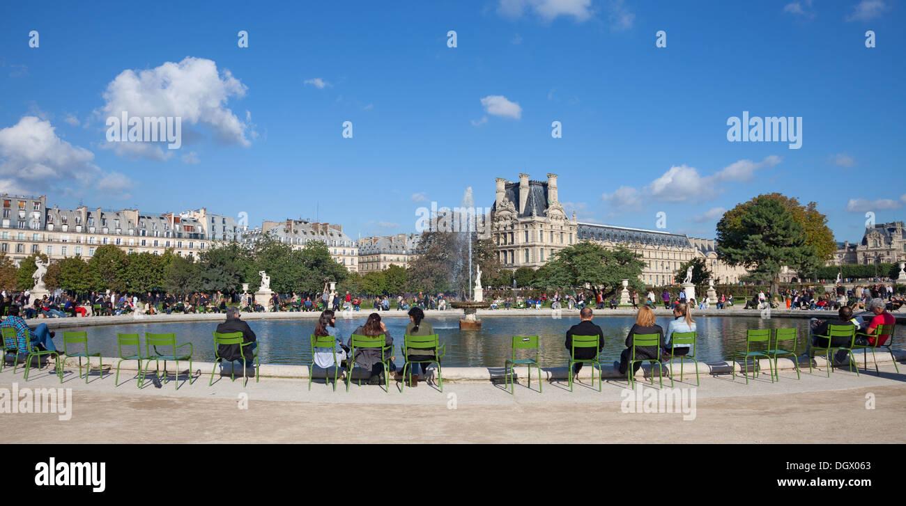 Les personnes bénéficiant du soleil d'automne autour d'un étang (Grand Bassin Rond) dans le Jardin des Tuileries, Paris. Le musée du Louvre est à l'arrière-plan Photo Stock