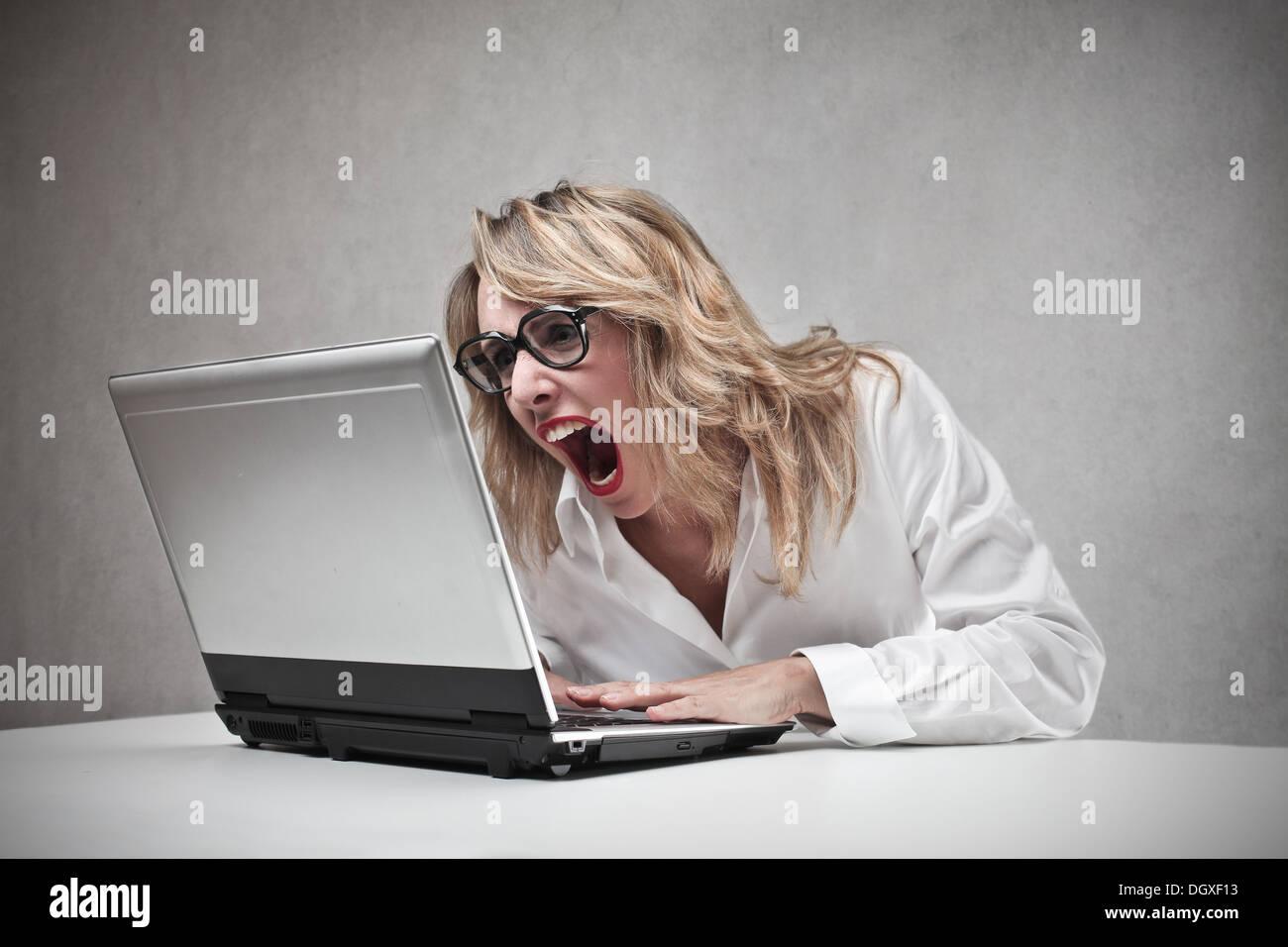 Femme blonde en colère crier contre un ordinateur portable Photo Stock