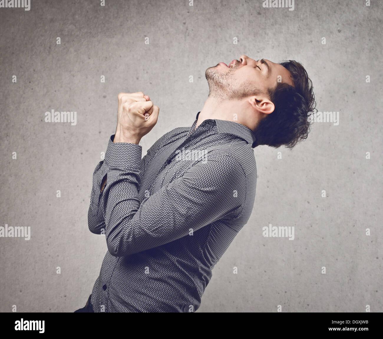 Jeune homme en chemise grise se réjouir de son succès Photo Stock