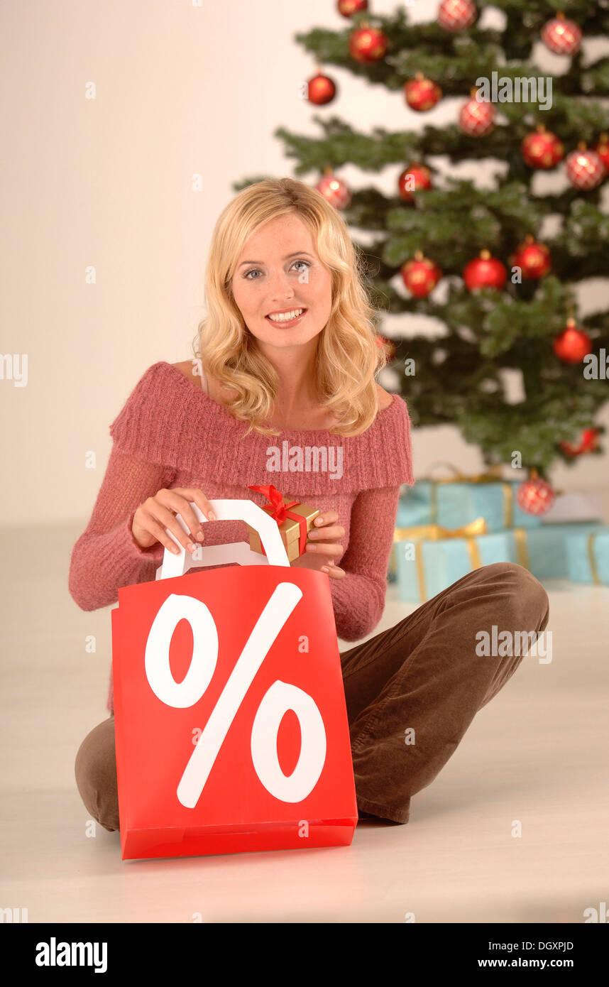 Femme blonde, 20-30, tenant un sac de magasinage d'un pourcentage, ambiance de Noël Photo Stock