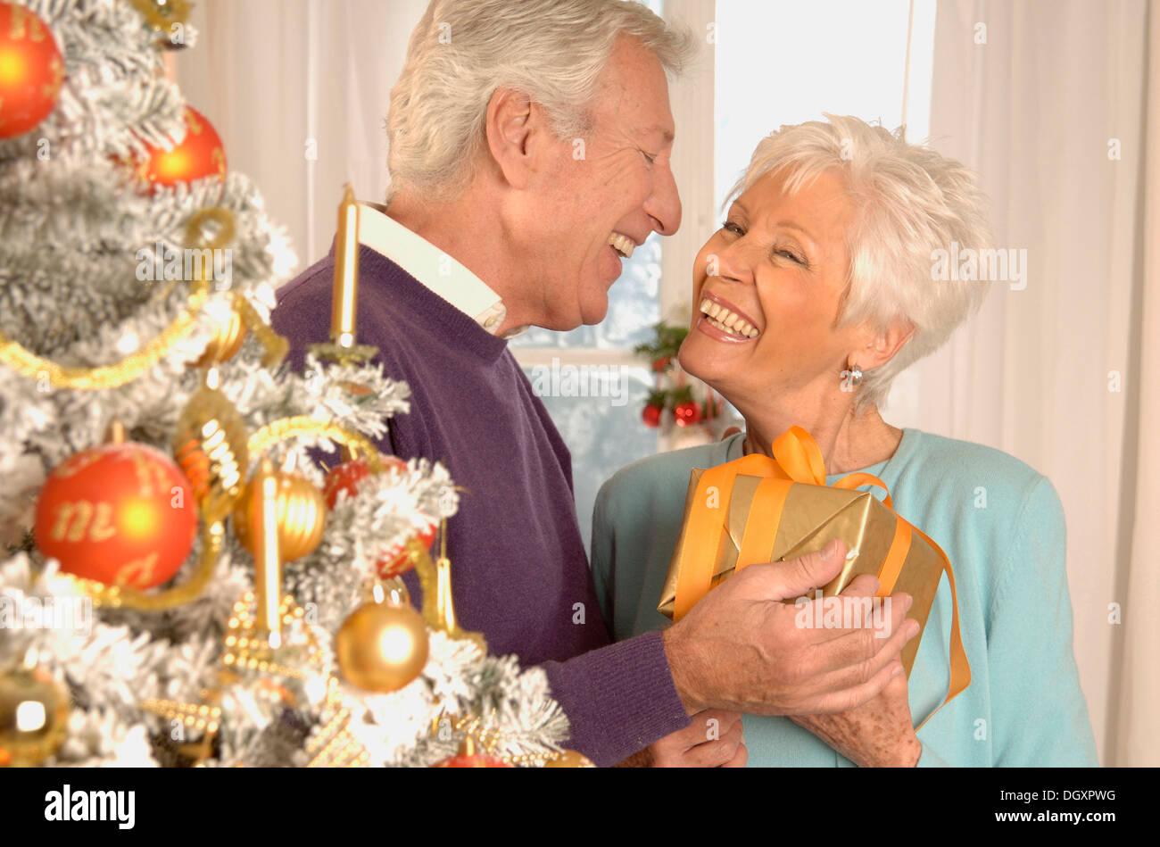 D'âge mûr à présent à côté d'un arbre de Noël Photo Stock