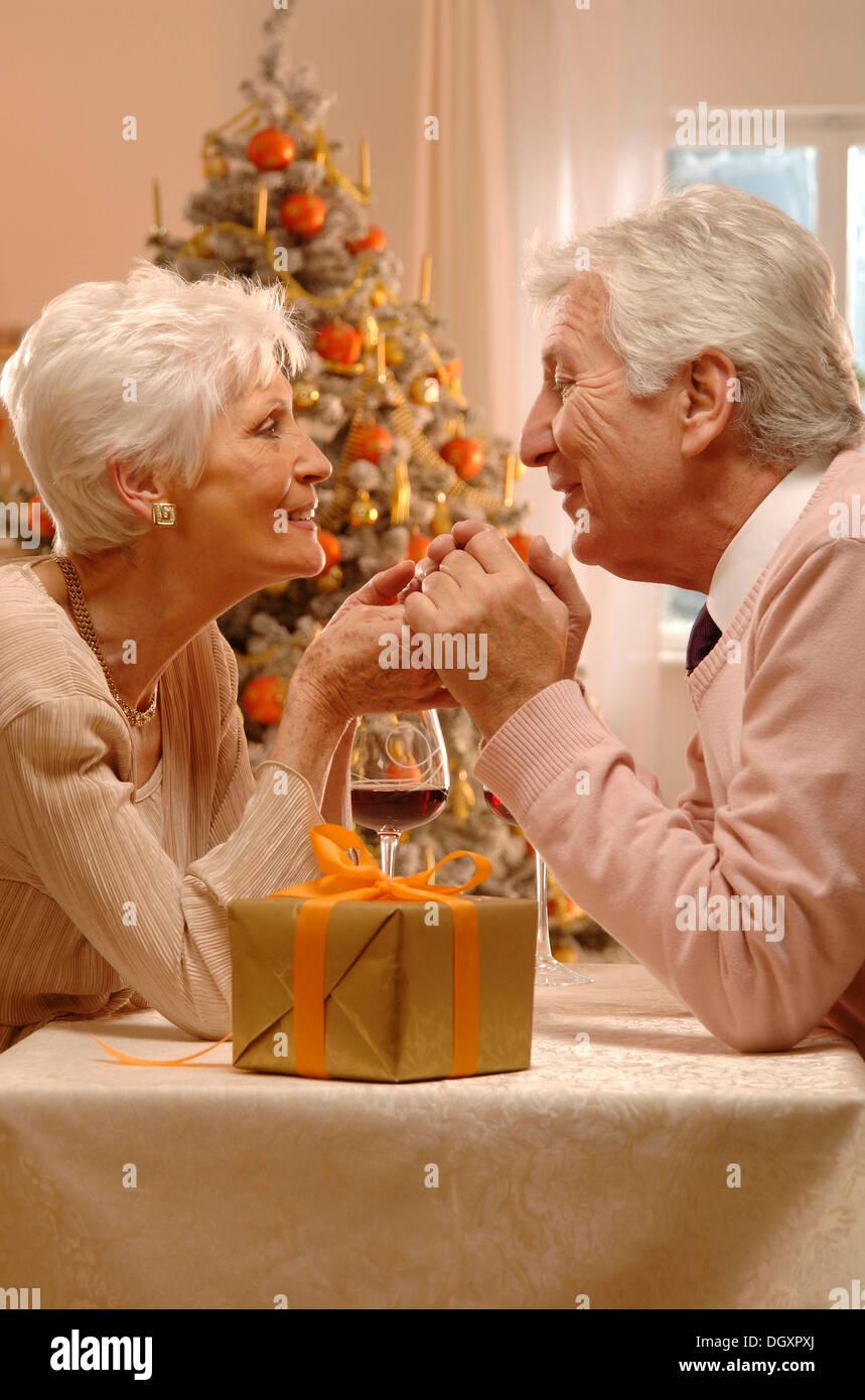 D'âge mûr avec des verres à vin rouge et un présent assis devant un arbre de Noël Photo Stock
