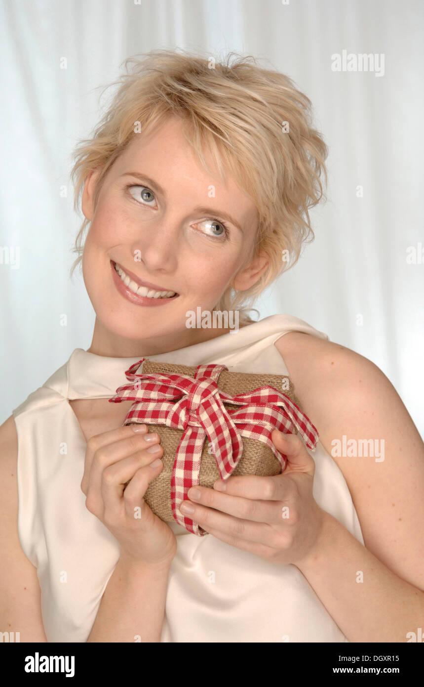 Femme blonde est heureux, maintenant présente dans ses mains Photo Stock