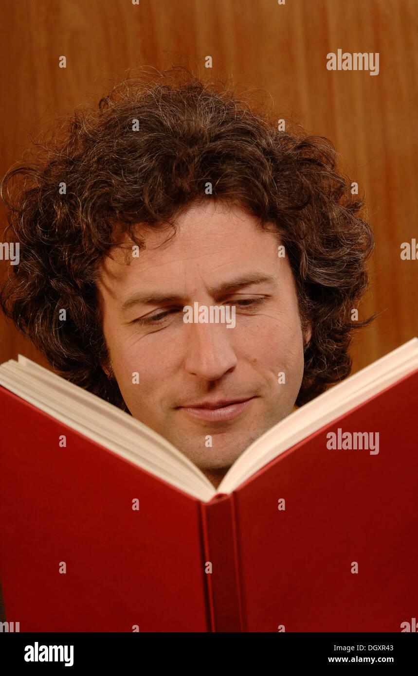 L'homme, 30-40, lire un livre rouge Photo Stock