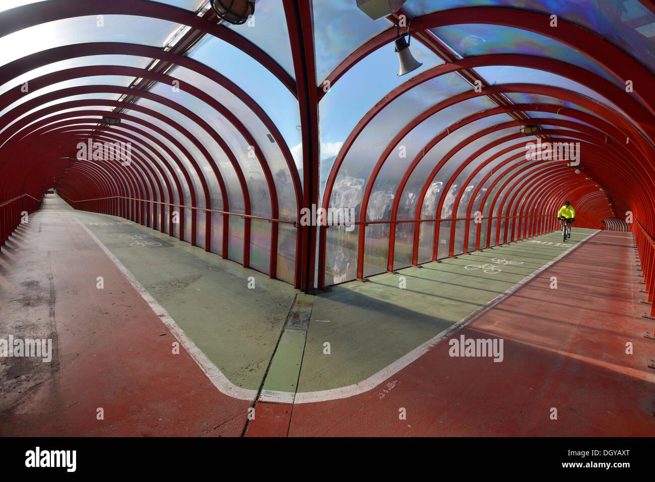Cycliste est à cheval sur une passerelle couverte et location pont, Glasgow, Ecosse, Royaume-Uni Banque D'Images