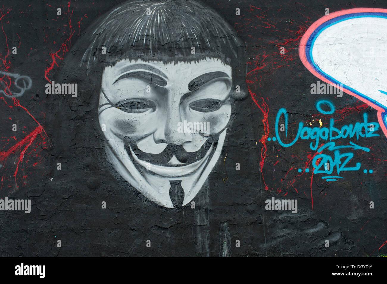 """Le Graffiti d'un homme avec un """"Anonyme"""" ou """"Guy Fawkes' masque, symbole de la 'occuper' mouvement de protestation contre le pouvoir de la Photo Stock"""