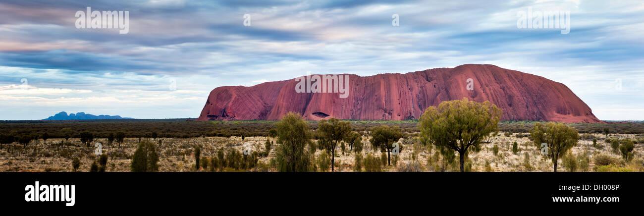 L'Uluru ou Ayers Rock avec les Olgas ou Katja Tjuta sur l'horizon, le Parc National d'Uluru-Kata Tjuta, Territoire du Nord, Australie Photo Stock