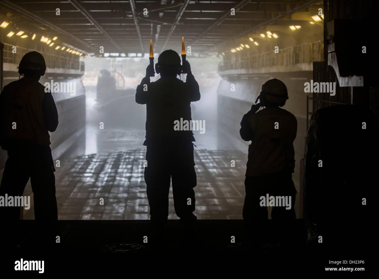 Boatswain's mates d'ordonner un landing craft air cushion (LCAC) dans le pont du coffre du navire d'assaut amphibie USS Kearsarge (DG 3). Kearsarge est déployée dans le cadre du groupe amphibie Kearsarge appuyer les opérations de sécurité maritime et le théâtre Photo Stock