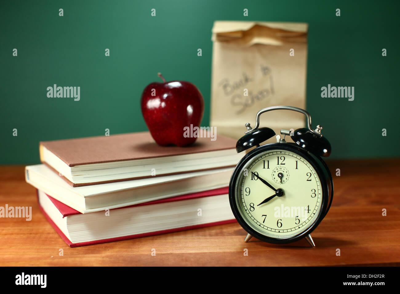 Apple horloge et pile de livres sur un bureau pour la rentrée