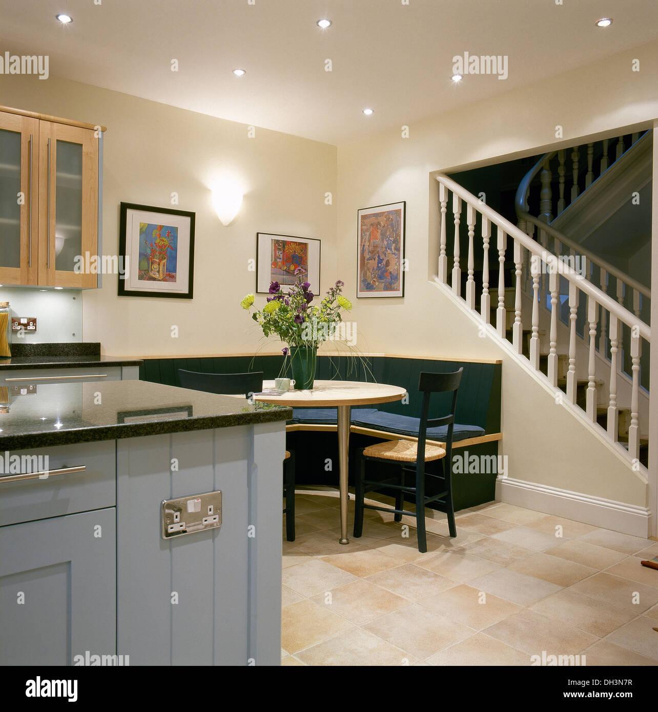 Corner de banquettes à table dans une cuisine moderne avec unité bleu pâle et escalier à