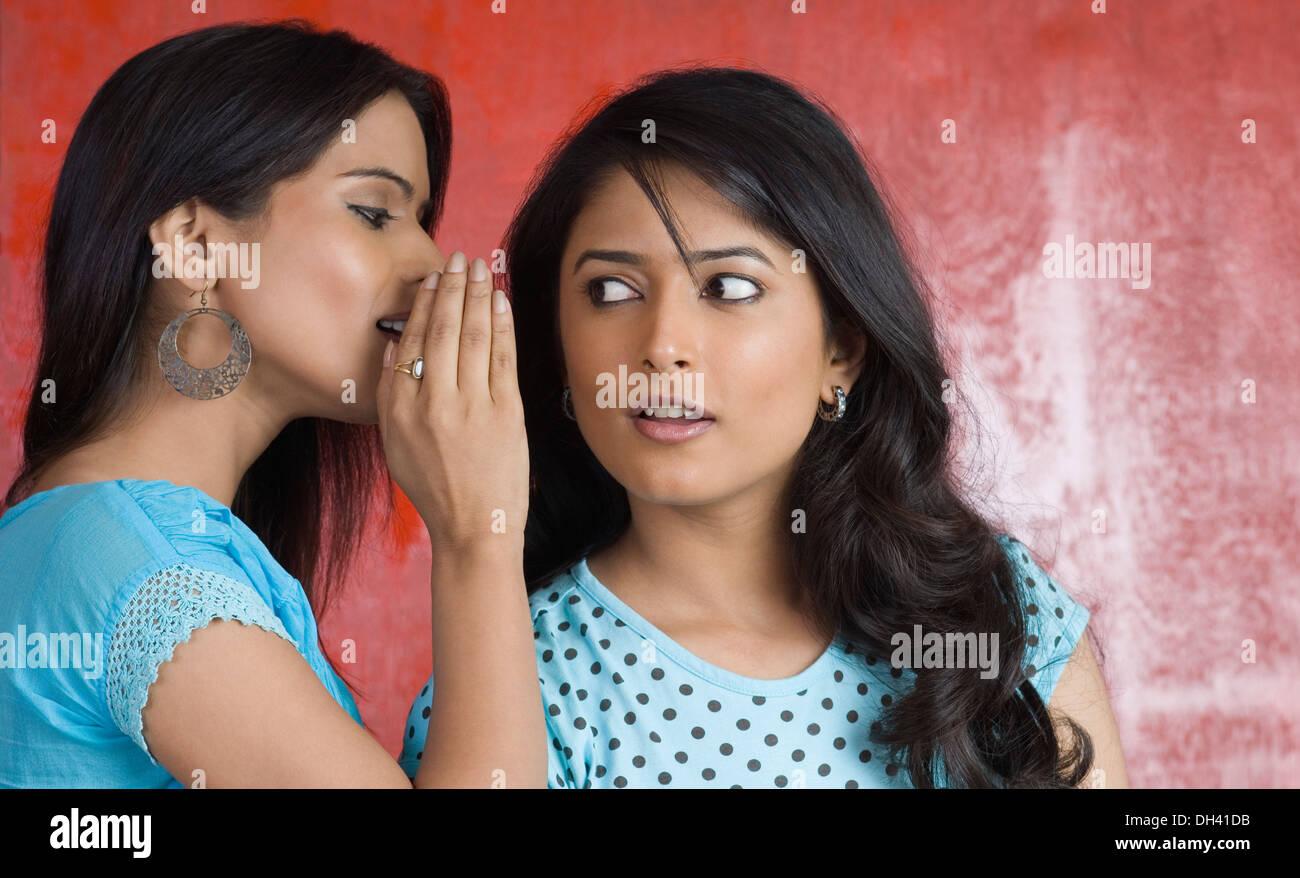 Teenage girl whispering à une jeune femme Banque D'Images