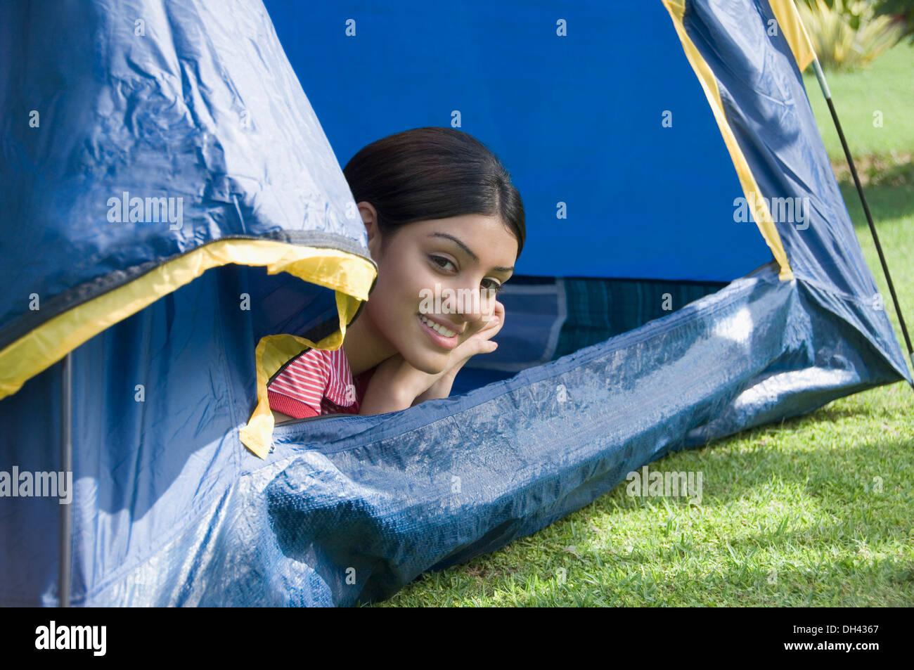 Femme couchée dans une tente et souriant Banque D'Images