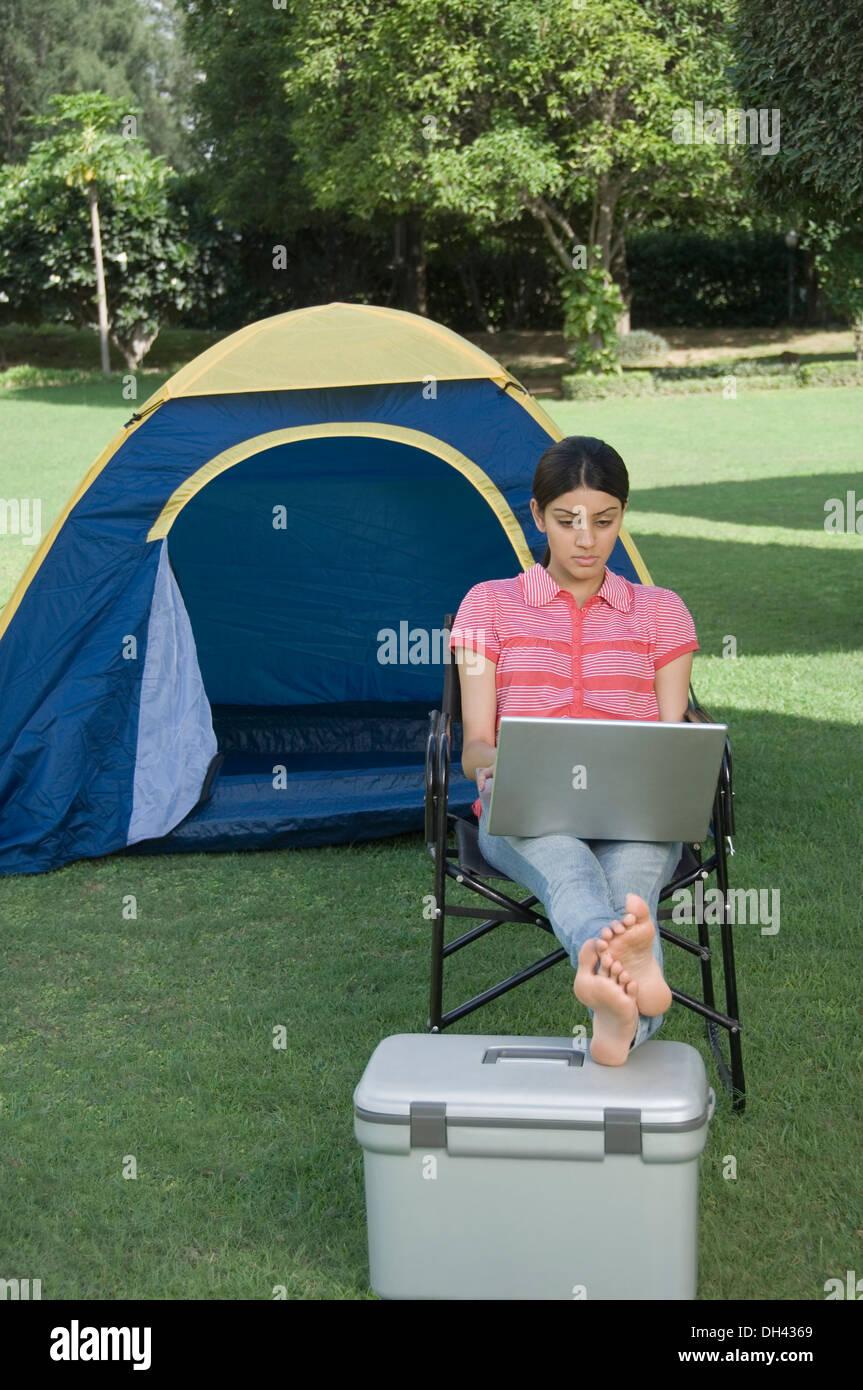 Woman using a laptop in a park Banque D'Images