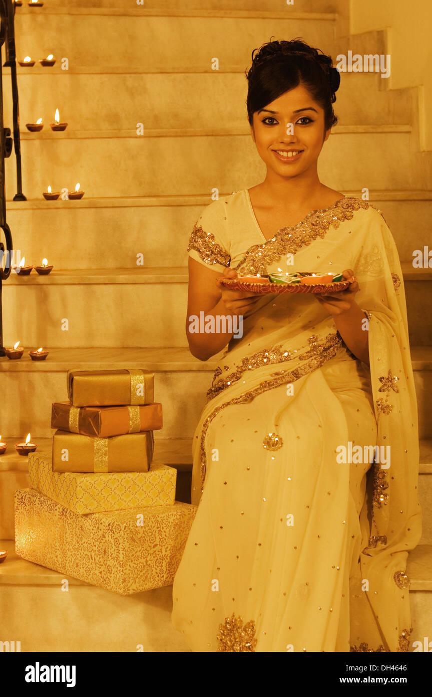Femme assise sur un escalier et la tenue d'offrande religieuse Banque D'Images