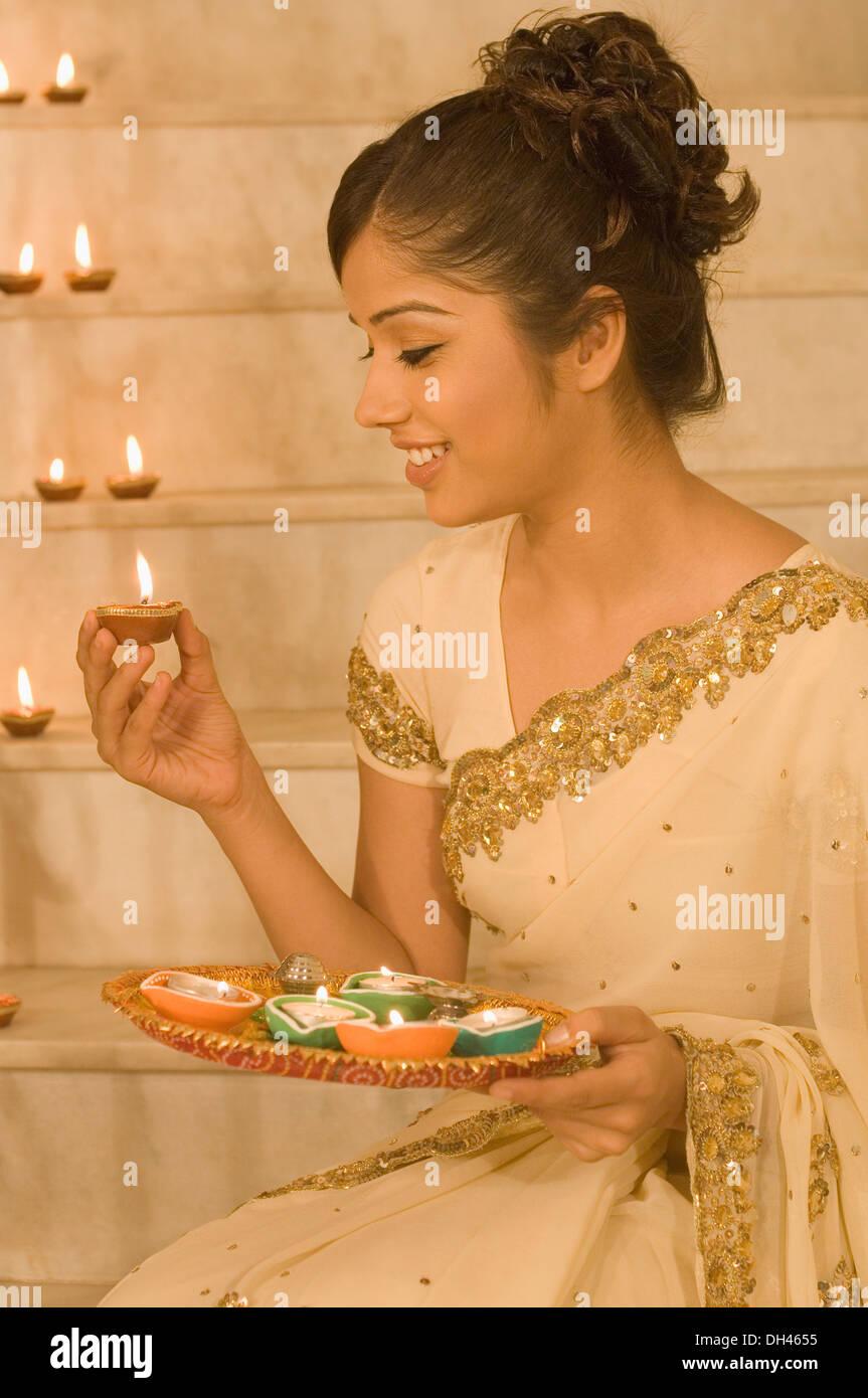 Femme tenant une lampe à huile et souriant Banque D'Images