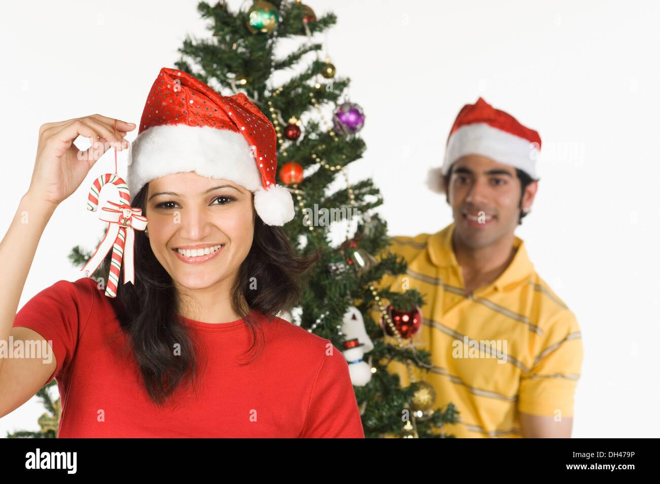 Femme montrant une canne avec un homme de décorer un arbre de Noël dans l'arrière-plan Banque D'Images