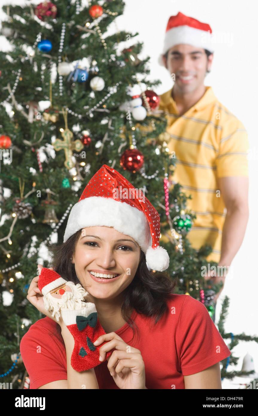 Femme montrant un homme avec un bas de Noël décorer un arbre de Noël dans l'arrière-plan Banque D'Images