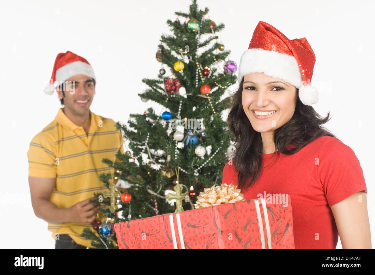 Femme tenant un cadeau de Noël avec un homme la décoration d'un arbre de Noël dans l'arrière-plan Banque D'Images