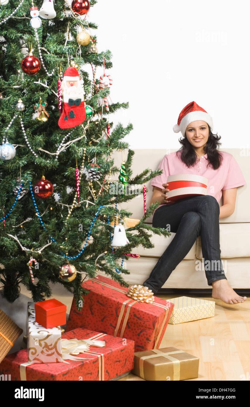 Femme assise sur un canapé près d'un arbre de Noël et smiling Banque D'Images