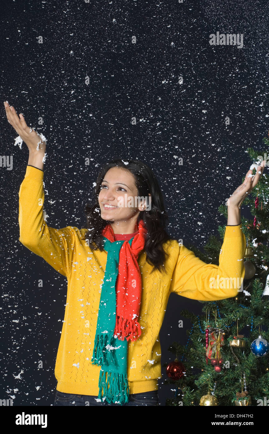 Femme debout dans la neige près d'un arbre de Noël Banque D'Images