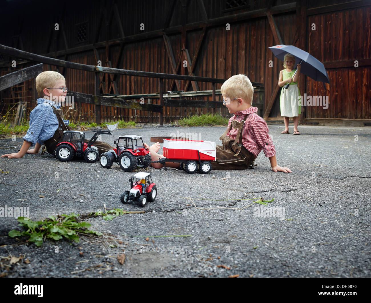Enfants jouant avec des tracteurs-jouets à la ferme, Reith im Alpbachtal, district de Kufstein, Tyrol du Nord, Tirol, Autriche Photo Stock