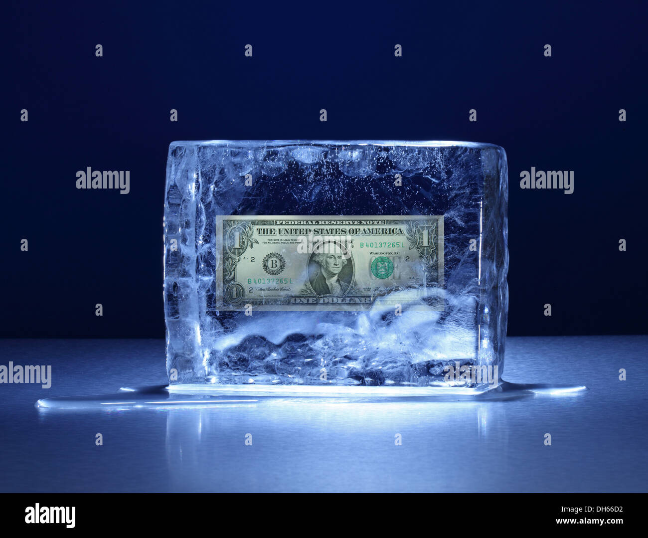 Un billet de un dollar US congelé dans un bloc de glace claire Photo Stock
