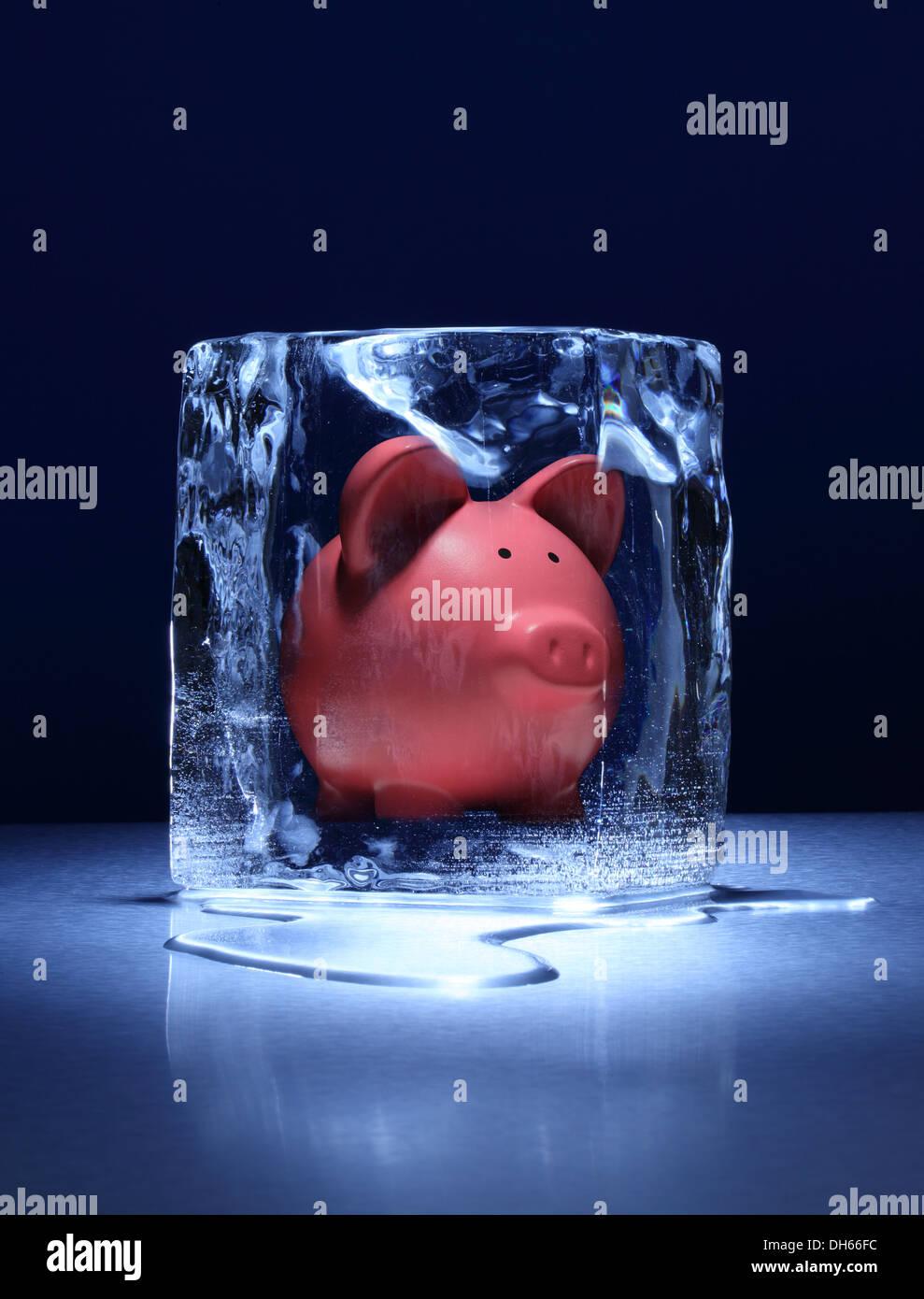Un argent rose tirelire congelé dans un bloc de glace claire Photo Stock