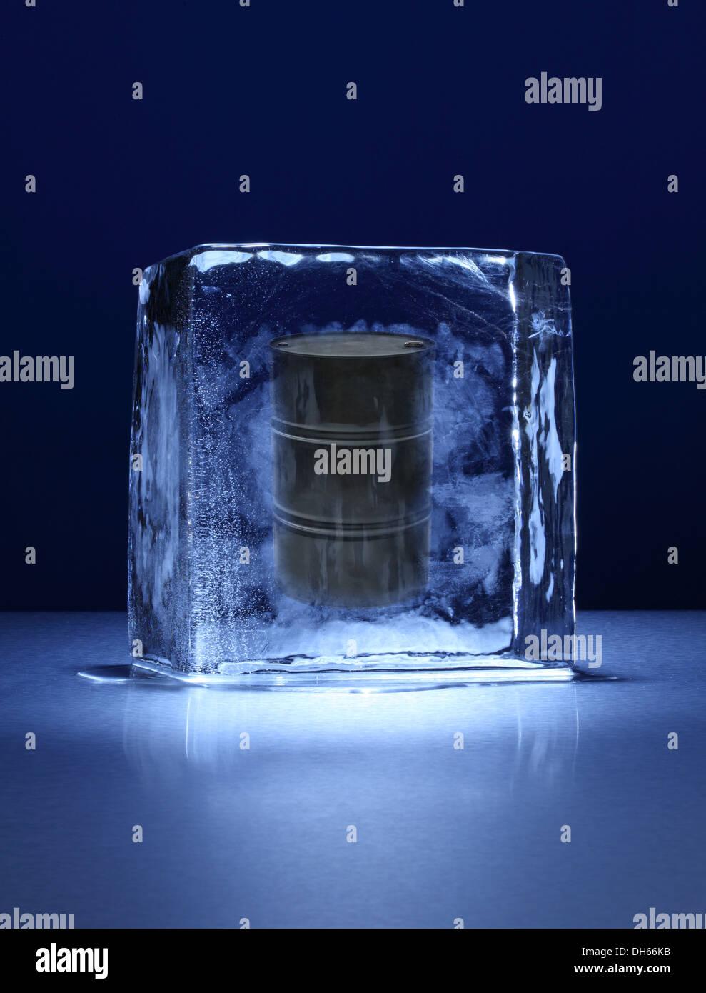 Un baril de pétrole noir congelé dans un bloc de glace claire Photo Stock