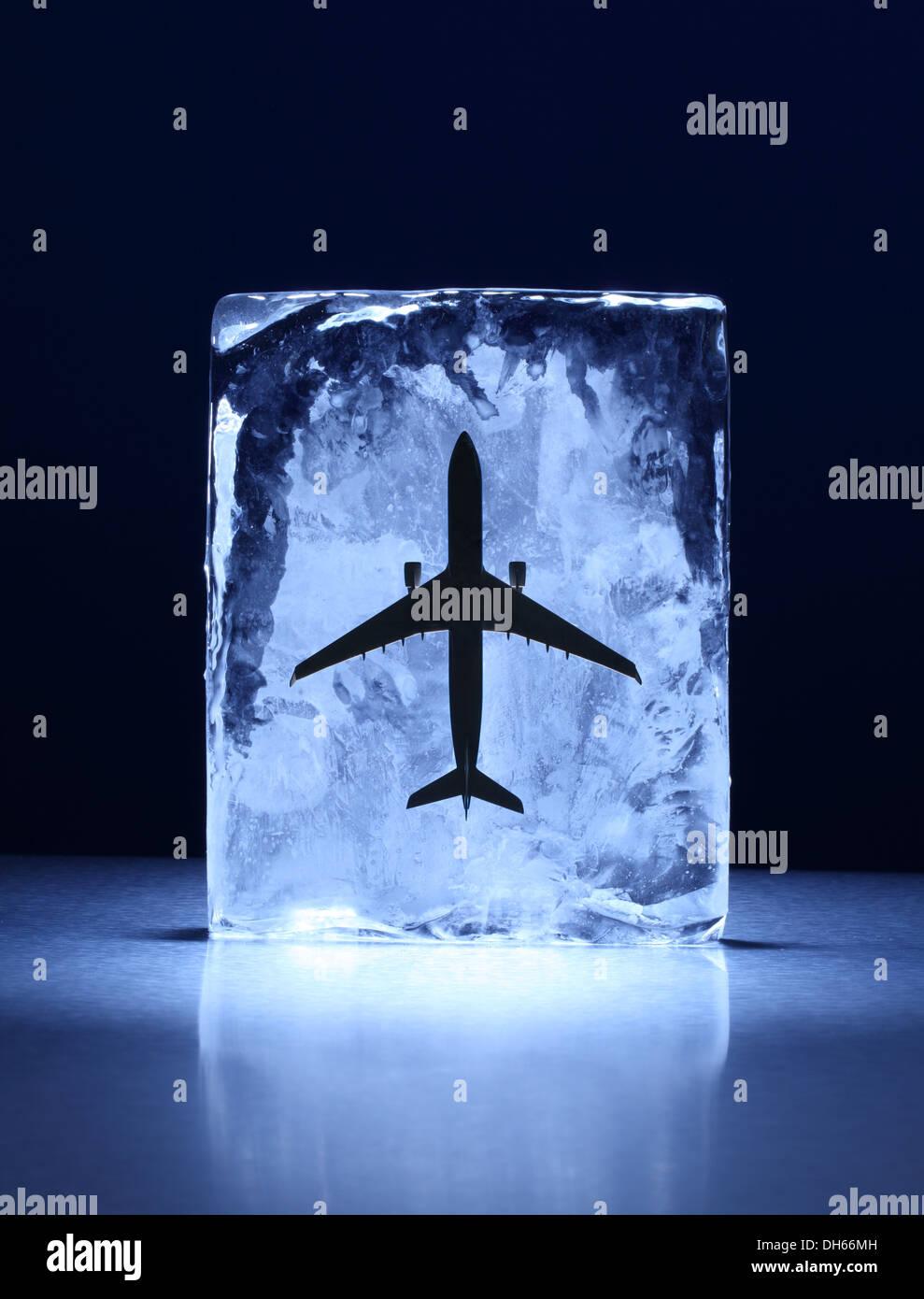 Un modèle réduit d'avion congelé dans un bloc de glace claire Photo Stock