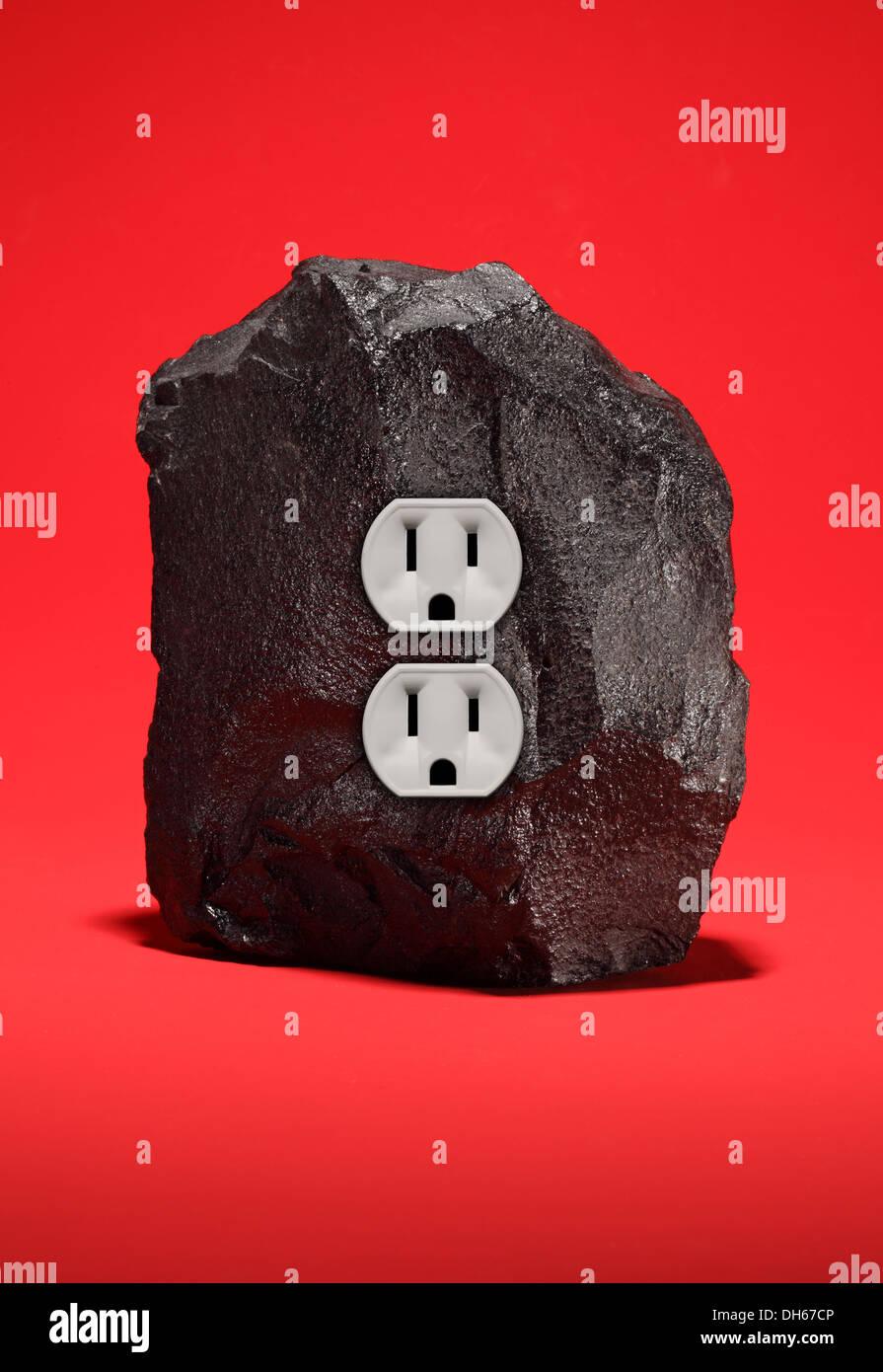 Un grand morceau de charbon noir avec une prise électrique double. Fond rouge brillant Photo Stock