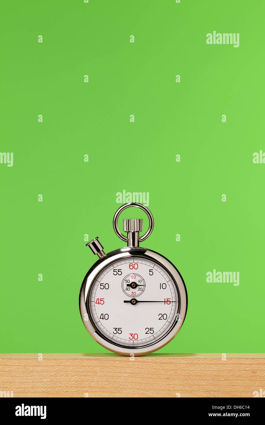 Un chronomètre sur une planche en bois avec un fond vert clair Photo Stock