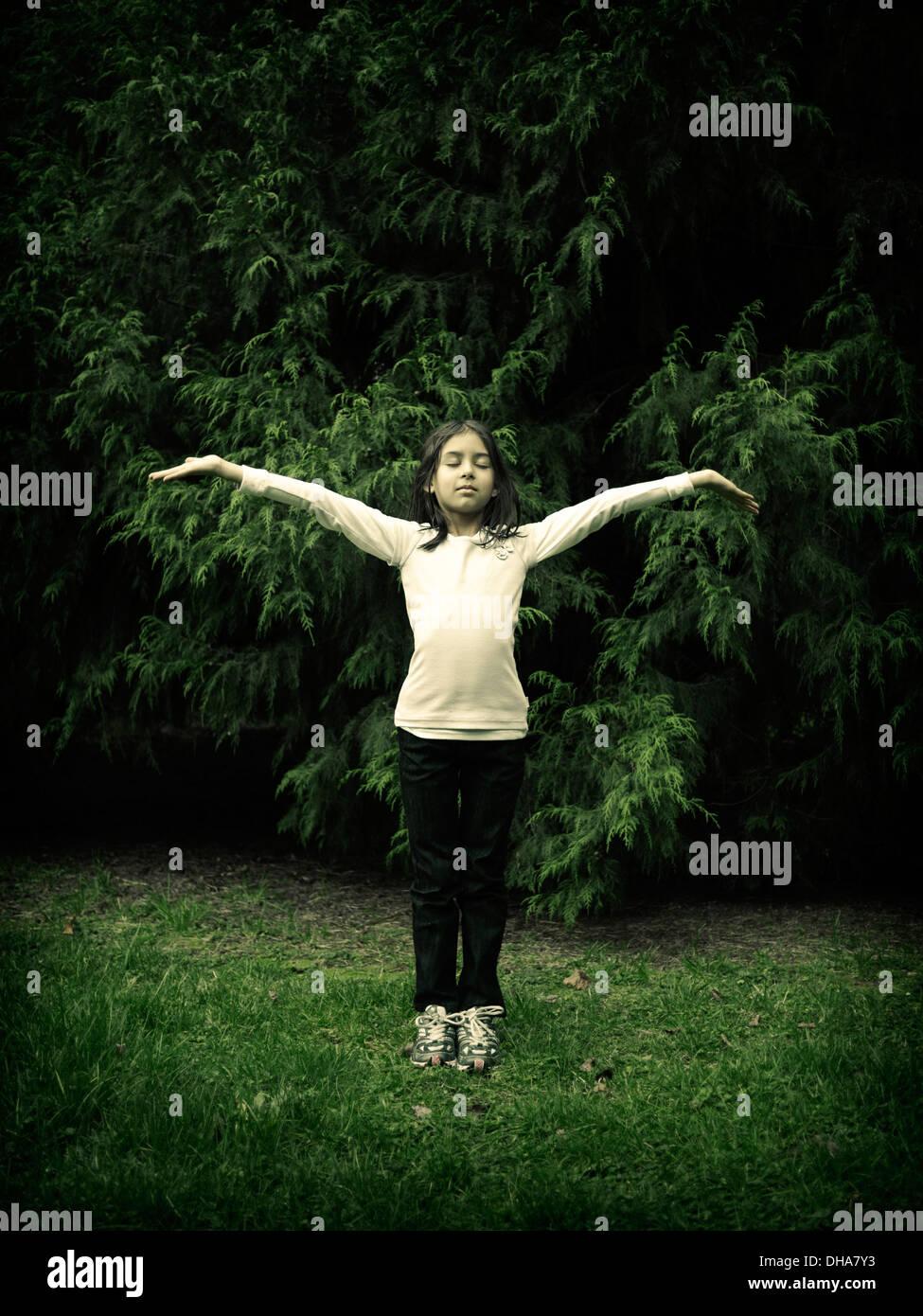 Jeune fille, les bras, les yeux fermés, les Conifères Photo Stock