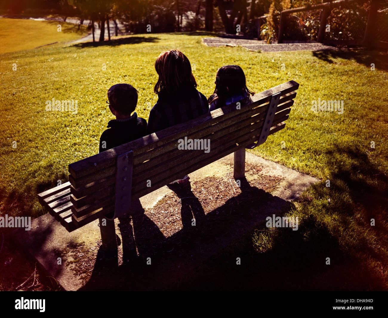 La mère, le fils et la fille s'asseoir sur le banc de parc sur journée d'hiver ensoleillée Banque D'Images