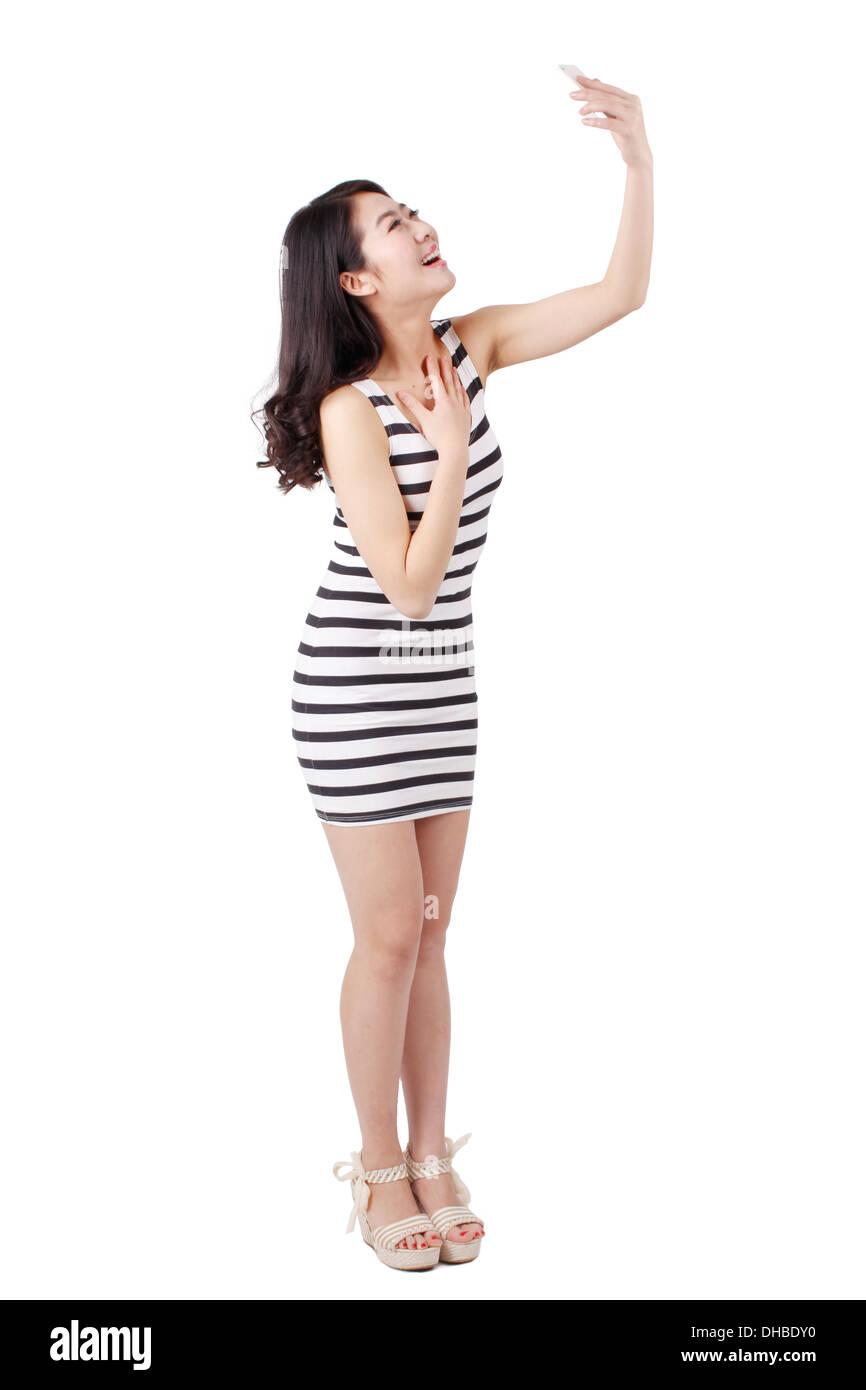 Jeune femme dans une robe rayée,photo prise avec un téléphone cellulaire Banque D'Images