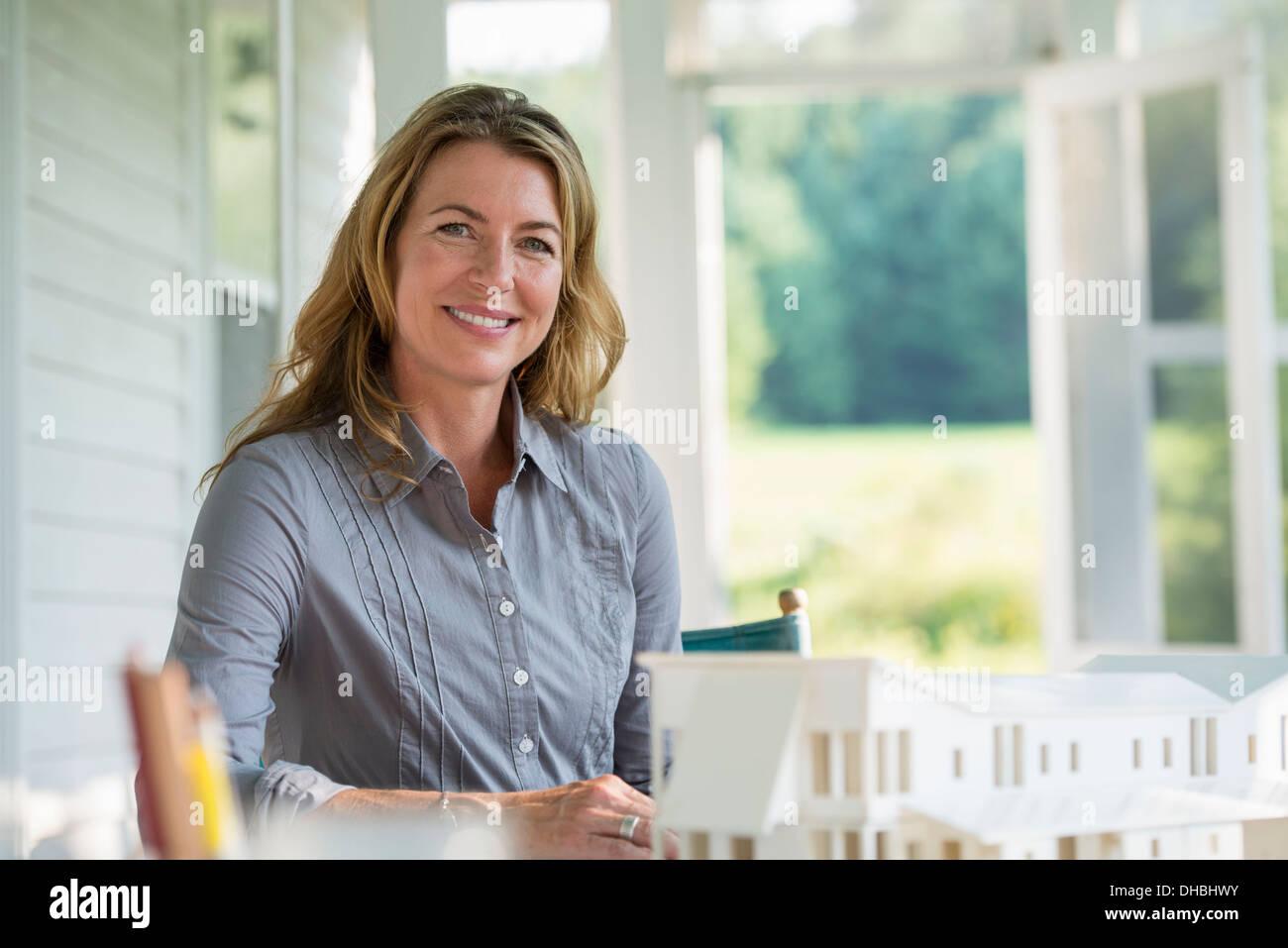 Une cuisine de la ferme. Un modèle d'une maison sur la table. La conception d'une maison. Une femme assise tenant un stylo. Photo Stock