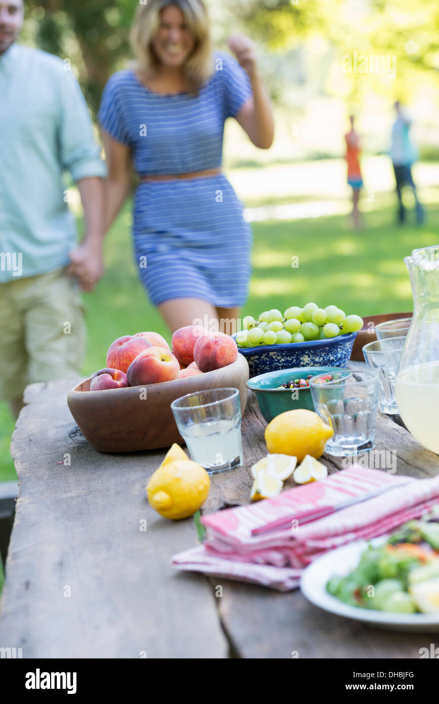 L'été un buffet de fruits et légumes, disposés sur une table. Les gens à l'arrière-plan. Photo Stock