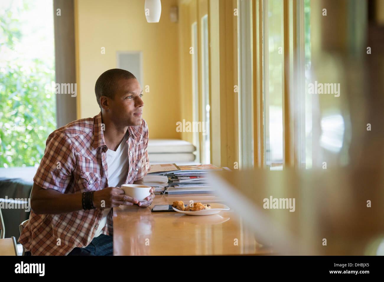 Un homme assis avec une tasse de café, tenant une tablette numérique. Photo Stock